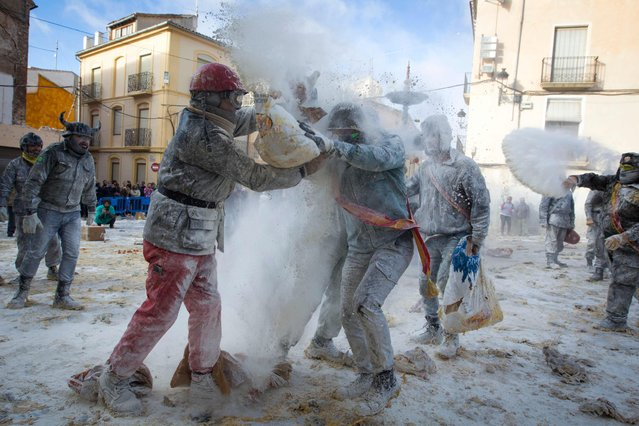 """Revellers dressed in mock military garb take part in the """"Els Enfarinats"""" battle in the southeastern Spanish town of Ibi on December 28, 2017. During this 200-year-old traditional festival participants known as Els Enfarinats (those covered in flour) dress in military clothes and stage a mock coup d'etat as they battle using flour, eggs and firecrackers outside the town hall as part of the celebrations of the Day of the Innocents. (Photo by Jaime Reina/AFP Photo)"""