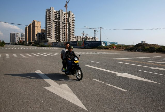 Men ride a motorbike through the largely empty the New Zone urban development in Dandong, Liaoning province, China September 11, 2016. (Photo by Thomas Peter/Reuters)