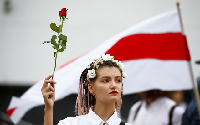 A woman holds a flower as she attends an opposition demonstration to protest against presidential election results in Minsk, Belarus on August 22, 2020. (Photo by Vasily Fedosenko/Reuters)