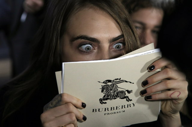 British model Cara Delevingne reacts as she attends a festive launch to mark the collaboration between top Paris department store Printemps and British fashion brand Burberry, in Paris, France, Thursday, November 6, 2014. (Photo by Francois Mori/AP Photo)