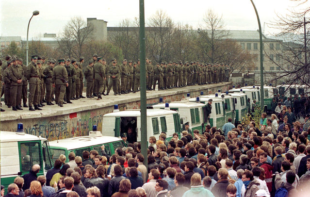 Hundreds of East Berlin border guards stand atop the Berlin Wall at the Brandeburg Gate faced by thousands of West Berliners on November 11, 1989. (Photo by Reuters/Stringer)