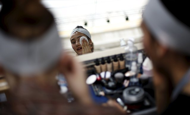 A model cleans her make-up backstage before designer Nadir Tati's collection show during Lisbon Fashion Week in Portugal October 11, 2015. (Photo by Rafael Marchante/Reuters)