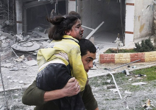 A man carries his sister, who was wounded in a government air strike, in Aleppo, Syria, on February 3, 2013. The Britain-based activist group, Syrian Observatory for Human Rights, said government troops bombarded a building in Aleppo's rebel-held neighborhood that killed more than10 people, including at least five children. (Photo by Abdullah al-Yassin/Associated Press)
