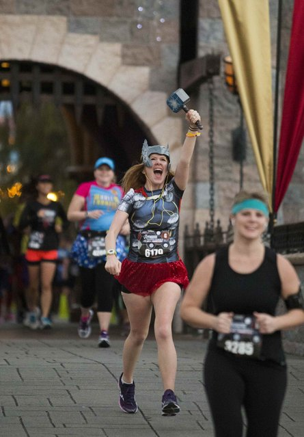 Abigail Crouse lifts her Thor hammer high after running through Sleeping Beauty's Castle during the Avengers Super Heroes Half Marathon in and around the Disney Parks in Anaheim, California November 16, 2014. Walt Disney Co has moved aggressively into the race business, attracting tens of thousands of runners every year to its marathons, half-marathons and family-friendly races. (Photo by Eugene Garcia/Reuters)
