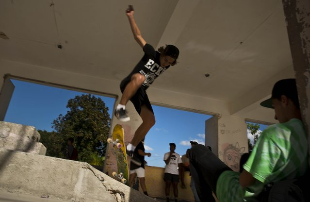 In this January 11, 2018 photo, a skater jumps during the inauguration of a new recreational space for skateboarders, created in an abandoned gym at the Educational complex Ciudad Libertad, a former military barracks that the late Fidel Castro turned into a school complex after the revolution in Havana, Cuba. Using small donations from individuals and a handful of charities, a group of Cuban skaters poured concrete bowls and ramps to create the facility for skaters. (Photo by Ramon Espinosa/AP Photo)