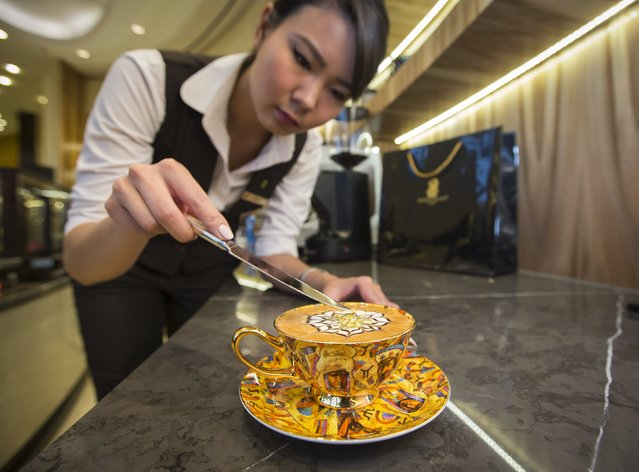 """Assel Utelbayeva, a barista from the Ritz-Carlton hotel, places eatable gold flakes into a cup of cappuccino called """"The Golden Horde"""" in Almaty, Kazakhstan, October 16, 2015. The Ritz-Carlton hotel offers cup of coffee worth 3000 Tenge (10.8 USD) marking the 550th anniversary of the Kazakh khanate. Three cups were sold since the launch of the promotion on October 15. (Photo by Shamil Zhumatov/Reuters)"""