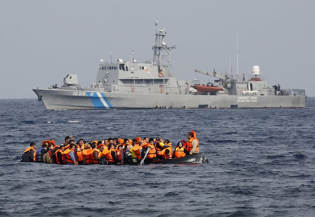 Syrian refugees call for help and empty water from their flooding raft as they approach  the Greek island of Lesbos past a Greek coast guard vessel October 20, 2015.Thousands of refugees – mostly fleeing war-torn Syria, Afghanistan and Iraq – attempt daily to cross the Aegean Sea from nearby Turkey, a short trip but a perilous one in the inflatable boats the migrants use, often in rough seas. (Photo by Yannis Behrakis/Reuters)