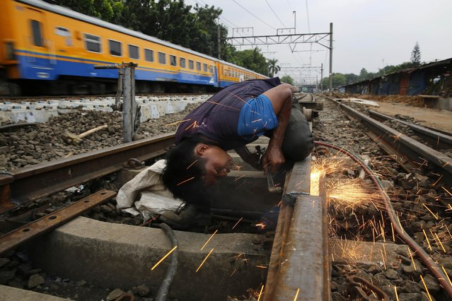 A labourer cuts railway track during repairs to the track bed on section of line in East Jakarta November 26, 2014. Needing some $450 billion spent on Indonesia's infrastructure by 2019, new President Joko Widodo has ordered ministers to give private investors first pick of money-making projects rather than let state agencies grab them as they usually do. (Photo by Darren Whiteside/Reuters)