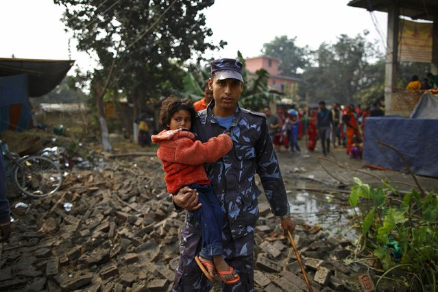 "A police officer carries a girl to the lost and found camp after she got lost in the crowd during the ""Gadhimai Mela"" festival held in Bariyapur November 29, 2014. (Photo by Navesh Chitrakar/Reuters)"