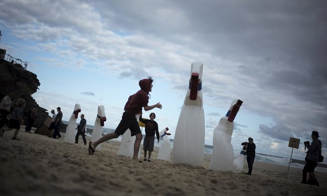 Children play around giant spray bottles by Australian artists from the RCM Collective on Tamarama Beach during the 19th annual Sculptures by the Sea exhibition in Sydney, October 23, 2015. (Photo by Jason Reed/Reuters)
