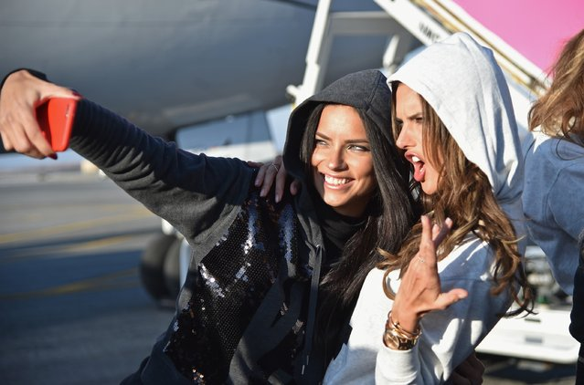 Victoria's Secret Models Adriana Lima (L) and Alessandra Ambrosio pose for a picture before they depart for London for the 2014 Victoria's Secret Fashion Show at JFK Airport on November 30, 2014 in New York City. (Photo by Mike Coppola/Getty Images for Victoria's Secret)