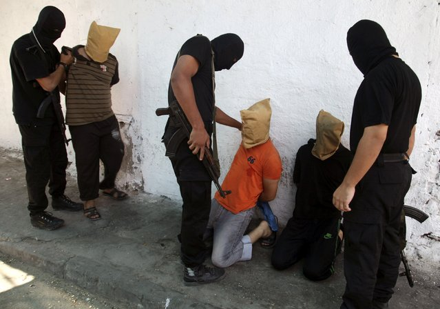Hamas militants grab Palestinians suspected of collaborating with Israel, before executing them in Gaza City, in this August 22, 2014 file photo. (Photo by Reuters/Stringer)