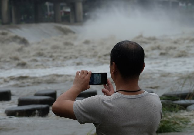 A local resident takes a photo at Xindian river in the aftermath of typhoon Megi at Xindian district in New Taipei City on September 28, 2016. (Photo by Sam Yeh/AFP Photo)