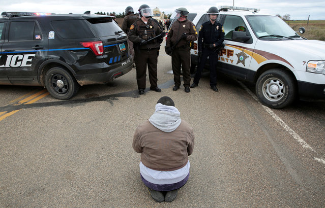 Caro Gonzales of Olympia, Washington, prays in front of police during a protest against the Dakota Access Pipeline between the Standing Rock Reservation and the pipeline route outside the little town of Saint Anthony, North Dakota, U.S., October 5, 2016. (Photo by Terray Sylvester/Reuters)