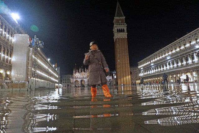 A woman walks in a flooded St. Mark's Square in Venice, Italy, Monday, March 12, 2018. High tides have flooded Venice, leading Venetians and tourists to don high boots and use wooden walkways to cross St. Mark's Square and other areas under water. (Photo by Andrea Merola/ANSA via AP Photo)