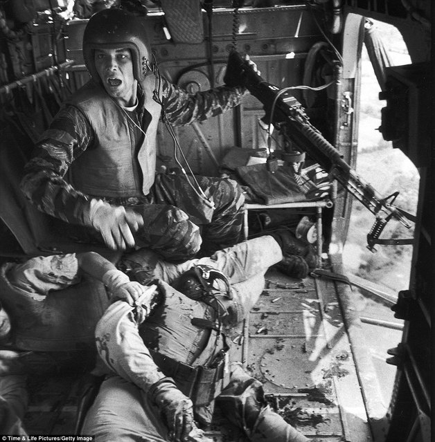"""Somebody help: James C. Farley (left) with a jammed machine gun shouts to crew as wounded pilot James E. Magel lies dying beside him"". (Photo by Larry Burrows/Time & Life Pictures)"