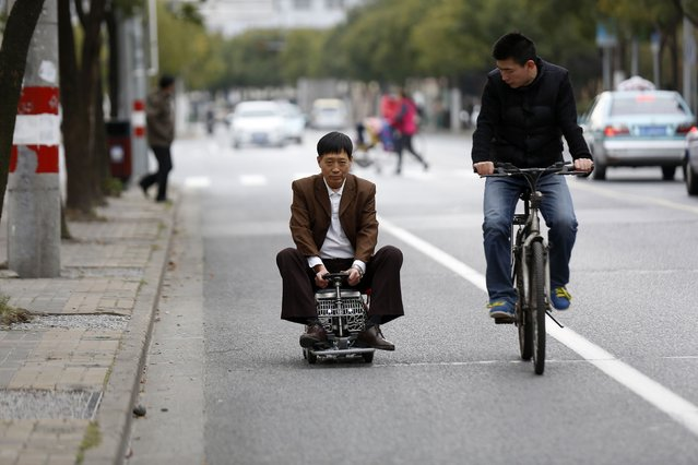 Xu Zhiyun (L), 60, drives his home-made motorised mini-vehicle along a street in Shanghai December 9, 2014. (Photo by Aly Song/Reuters)
