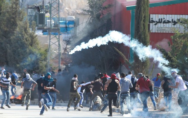 Palestinian protesters run away from tear gas canisters fired by Israeli troops during clashes in the West Bank city of Bethlehem October 31, 2015. (Photo by Abdelrahman Younis/Reuters)