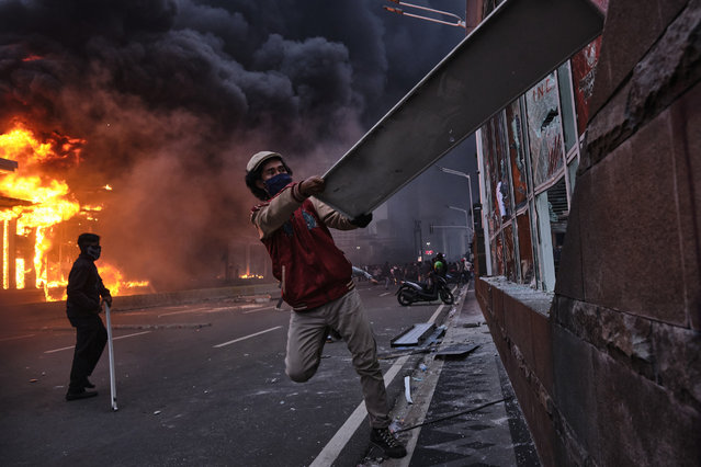 A rioter smashes the window of a building on October 8, 2020 in Jakarta, Indonesia. Protesters have gathered across Indonesia after the government passed a labor law it claims will boost economic recovery needed due to coronavirus. Critics claim the bill will worsen labor conditions and environmental protections. (Photo by Ed Wray/Getty Images)