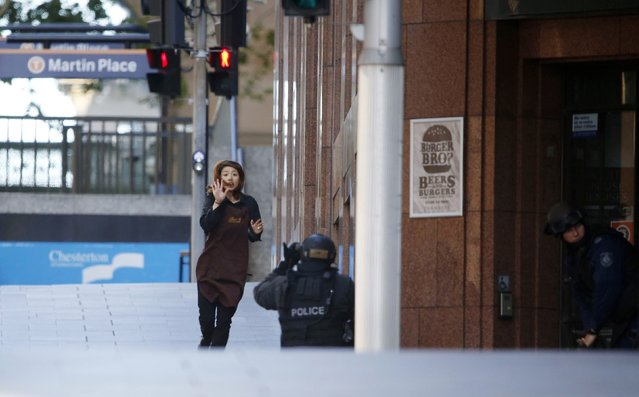 A hostage runs towards a police officer outside Lindt cafe, where other hostages are being held, in Martin Place in central Sydney December 15, 2014. (Photo by Jason Reed/Reuters)