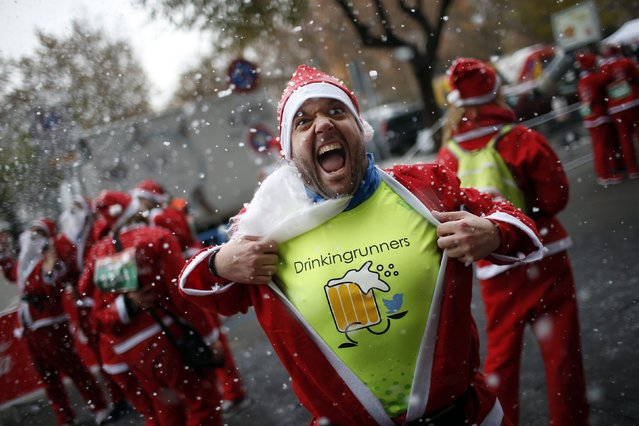 A man dressed in a Santa outfit reacts for the camera under artificial snow at the end of the annual Carrera de Papa Noel (Santa Claus Run), in Madrid, December 13, 2014. (Photo by Juan Medina/Reuters)