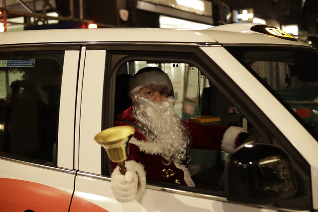 London taxi driver Michael Harris, dressed as Santa Claus, who said he was in hospital with coronavirus for three weeks earlier in the year, poses for photographs in his cab parked outside Burlington Arcade, during England's second coronavirus lockdown in London, Wednesday, November 25, 2020. With major COVID-19 vaccines showing high levels of protection, British officials are cautiously — and they stress cautiously — optimistic that life may start returning to normal by early April. (Photo by Matt Dunham/AP Photo)