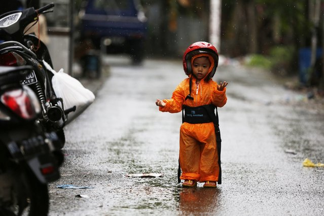 A boy wearing a raincoat and a helmet stands under the rain on a road in Pasar Atjeh in Banda Aceh December 25, 2014. (Photo by Reuters/Beawiharta)