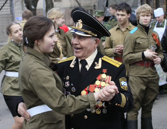 A World War Two veteran dances with a girl dressed in a Red Army uniform during a street performance ahead of Victory Day in the Russian Siberian city of Krasnoyarsk, May 7, 2013. (Photo by Ylia Naymushin/Reuters)
