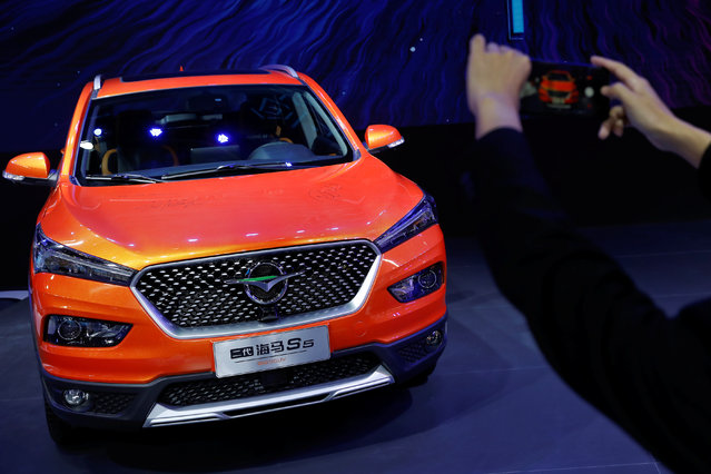 A visitor takes pictures of the S5 SUV by Haima Automobile Group during a media preview at the Auto China 2018 motor show in Beijing, China on April 25, 2018. (Photo by Damir Sagolj/Reuters)