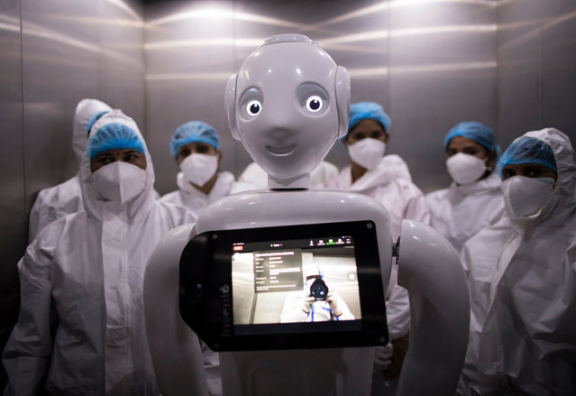 "A robot used to assist Covid-19 patients is seen in an elevator on December 5, 2020 in New Delhi, India. The ""Mitra"" robot can connect patients with their loved ones, and can assist healthcare workers on the frontlines of the pandemic by minimisng the risk of infections caused by close contact. The Yatharth Hospital, which is treating Covid-19 patients in Noida, on the outskirts of New Delhi, is one of a handful of hospitals in India that has started to use robots. (Photo by Anindito Mukherjee/Getty Images)"