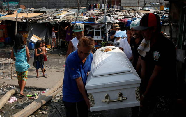 Mourners carry the coffin of Vicente Batiancila in a slum district where he lived, whom police said was among five victims of drug related killings three weeks ago, during his funeral in Navotas, Metro Manila in the Philippines, October 23, 2016. (Photo by Erik De Castro/Reuters)