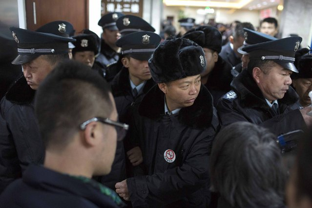 Policemen and security guards stand in front of family members as they wait at a hospital after a stampede occurred during a New Year's celebration on the Bund, a waterfront area in central Shanghai January 1, 2015. (Photo by Aly Song/Reuters)