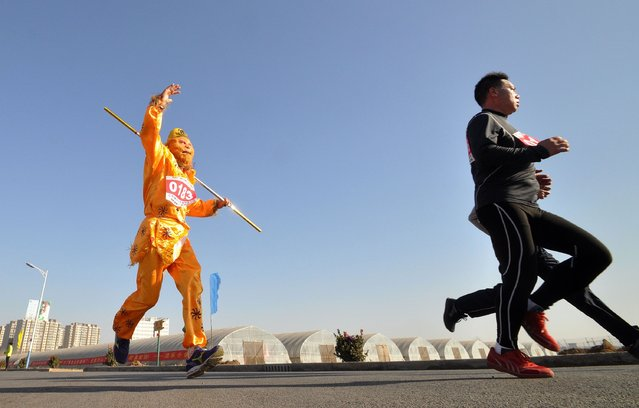 """A runner (L) dressed in a traditional Chinese """"monkey king"""" costume participates in a running competition to embrace the coming new year in Handan, in northern China's Hebei province on December 31, 2014. People from different part of China celebrate the coming 2015 in different ways according to their culture and traditions. (Photo by AFP Photo)"""