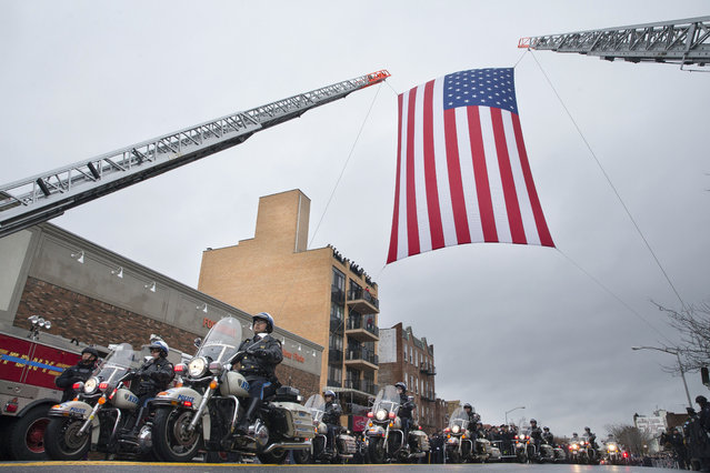 Motorcycle police officers ride under a giant American Flag as they lead the procession route during the funeral of New York Police Department Officer Wenjian Liu, Sunday, January 4, 2015, in the Brooklyn borough of New York. Liu and his partner, officer Rafael Ramos, were killed Dec. 20 as they sat in their patrol car on a Brooklyn street. The shooter, Ismaaiyl Brinsley, later killed himself. (Photo by John Minchillo/AP Photo)