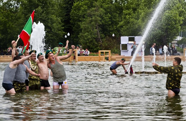 Russian border guards holding pose for a photo while bathing in a fountain in Moscow's Gorky Park as they celebrate the Border Guard's Day in Moscow, on May 28, 2013. (Photo by Misha Japaridze/Associated Press)