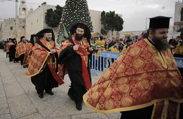 Members of the Greek Orthodox clergy wait for the arrival of the Greek Patriarch of Jerusalem Metropolitan Theophilos before the Eastern Orthodox Christmas procession outside the Church of the Nativity in the West Bank town of Bethlehem January 6, 2015. (Photo by Ammar Awad/Reuters)