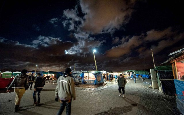 """Migrants and refugees walk through the makeshift migrant and refugee camp """"The Jungle"""" on November 25, 2015 in Calais, northern France. Clashes broke out November 25 between some 800 migrants and law enforcement on port bypass Calais (Pas-de-Calais), with seven minor injuries among the police and migrants, according to the prefecture of Pas-de-Calais. (Photo by Philippe Huguen/AFP Photo)"""