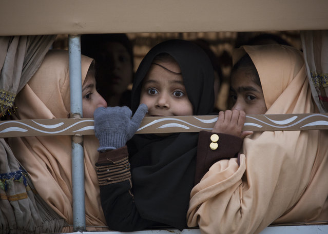 Pakistani students look out from a vehicle on their way to school near the Army Public School which was targeted by Taliban militants last year, in Peshawar, Pakistan, Monday, January 12, 2015. (Photo by B.K. Bangash/AP Photo)