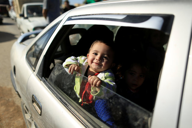 A boy who had just fled Kokjali near Mosul sits in a car along a road east of Mosul, Iraq November 3, 2016. (Photo by Zohra Bensemra/Reuters)