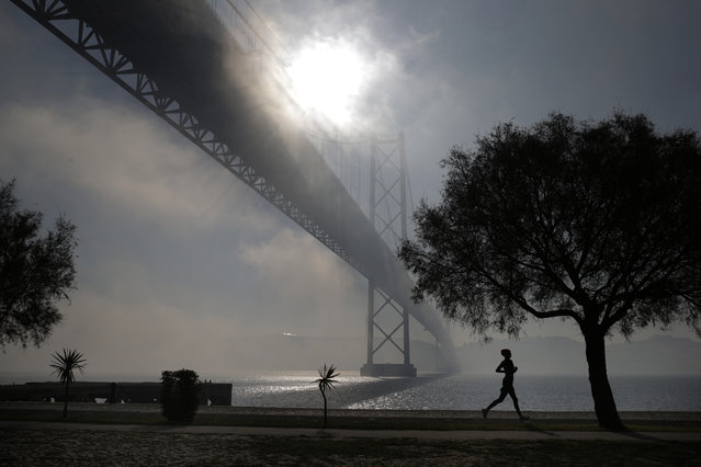 A woman jogs by the Tagus riverbank next to the April 25th bridge in Lisbon on a foggy morning, Monday, January 5, 2015. (Photo by Francisco Seco/AP Photo)