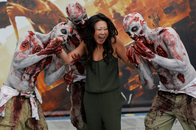 An attendee poses for a picture with zombies at E3, the world's largest video game industry convention in Los Angeles, California on June 12, 2018. (Photo by Mike Blake/Reuters)