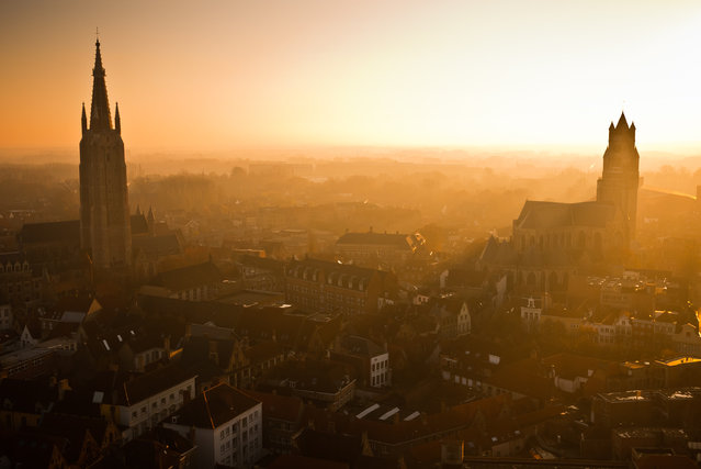 """Sunset over Bruges"". The Belgian city of Bruges is famous for its stunning medieval architecture. Taken at sunset on top of the Belfort, the city's gothic cathedral spires (the Church of Our Lady on the left, and St. Salvator's Cathedral on the right) and angular roofs are bathed by the warm glow of an ethereal, golden light. (Photo and caption by Calvin Lee/National Geographic Traveler Photo Contest)"