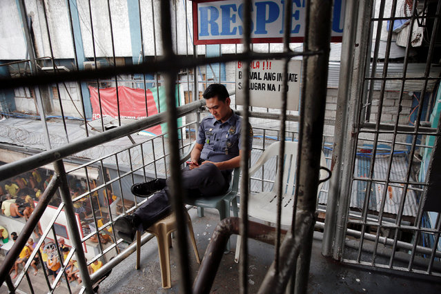 A security guard checks his phone as he watches over inmates inside Quezon City Jail in Manila, Philippines October 19, 2016. (Photo by Damir Sagolj/Reuters)