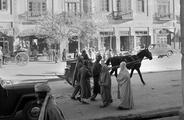 Women, wearing traditional burqas and Persian slippers, walk alongside men, cars and horse carts, in a street in Kabul, in 1951. At the time, this street was one of only three paved streets in the capital city. (Photo by AP Photo via The Atlantic)