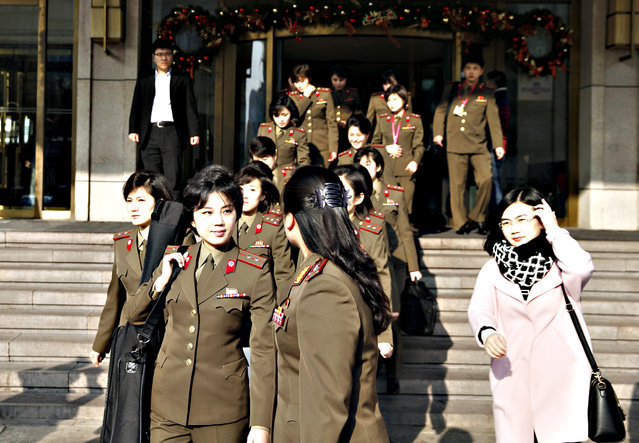 Members from North Korea's Moranbong band walk out of their hotel in Beijing on December 11, 2015. North Korea's premier pop group, the all-girl Moranbong band formed by leader Kim Jong-Un, is electrifying audiences in China in shows aimed at harmonising out-of-tune ties between the traditional allies, reports and the venue said on December 9 – but tickets are not available to the public. (Photo by AFP Photo)