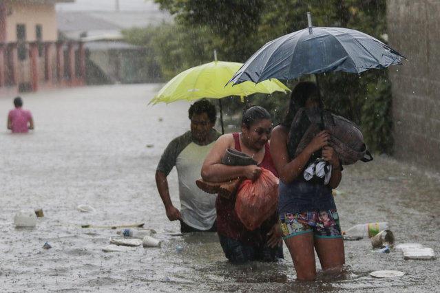 Residents wade through a flooded road carrying some belongings, in Progreso Yoro, Honduras, Wednesday, November 4, 2020. Eta weakened from the Category 4 hurricane to a tropical storm after lashing the Caribbean coast for much of Tuesday, its floodwaters isolating already remote communities and setting off deadly landslides. (Photo by Delmer Martinez/AP Photo)