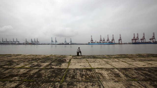 A man sits on the shore opposite to the closed Jawaharlal Nehru Port on the Elephanta Island on the outskirts of Mumbai in this August 12, 2010 file photo. India is expected to release trade data this week. (Photo by Danish Siddiqui/Reuters)