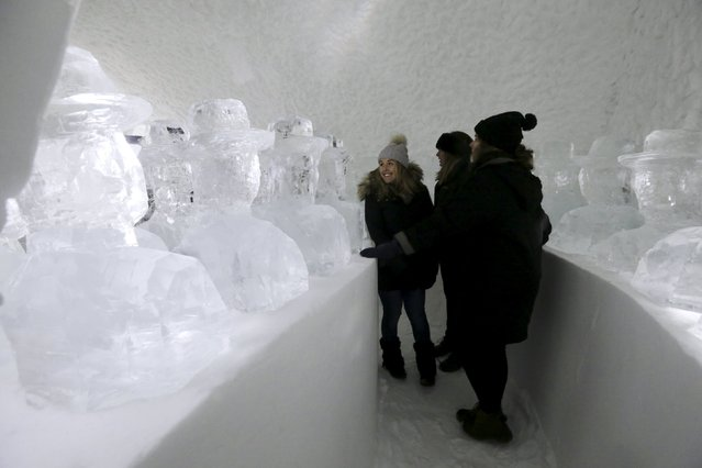 People observe ice sculptures in the room in the Ice hotel in Jukkasjarvi, Sweden, December 16, 2015. (Photo by Ints Kalnins/Reuters)