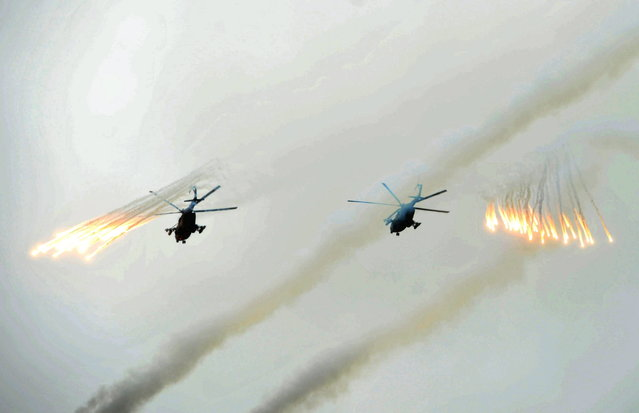 Russian Army helicopters fire flares over Sakhalin Island during military exercises on Tuesday, July 16, 2013. (Photo by Alexei Nikolsky/AP Photo/RIA Novosti/Presidential Press Service)