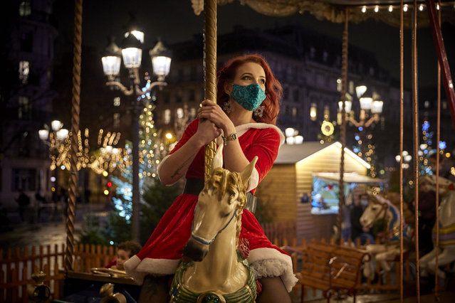 A Parisian enjoys the free traditional carousel at the Christmas Village at Hotel de Ville in Paris, as France prepares to exit from strict lockdown on Tuesday in time for Christmas on December 14, 2020 in Paris, France. France is trading its second nationwide lockdown for a more lenient curfew despite Covid-19 hospitalizations rising slightly in recent days, but are still within the range deemed acceptable for easing the restrictions imposed on October 30. However, bars, restaurants, museums, theatres and cinemas must remain shut until least the first week of January. (Photo by Kiran Ridley/Getty Images)